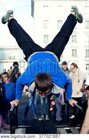 Norilsk, Russia - August, 28, 2016: Young Guy Athlete Does Exercise. Handstand On Uneven Bars On The