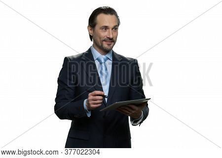 Smiling Businessman Is Writing On The Tablet. Successful Well-dressed Man With Pen Isolated On White