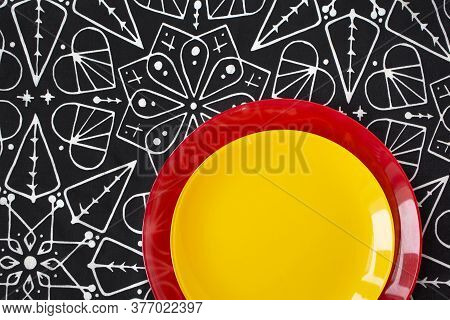 Bright Red And Yellow Plates Standing On Black And White Tablecloth. Energetic, Fresh And Contrast P