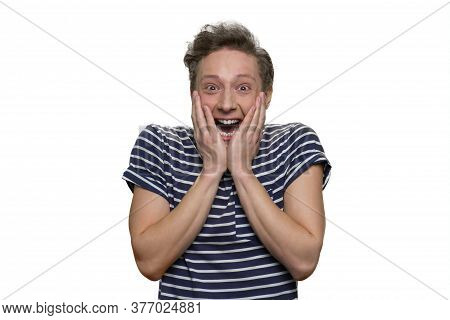 Happy Shocked Overwhelmed Teen Guy Is Touching His Face. Surprised And Astonished Young Guy Isolated