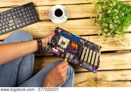 The Wire Is Inserted Into The Motherboard. Wood Background