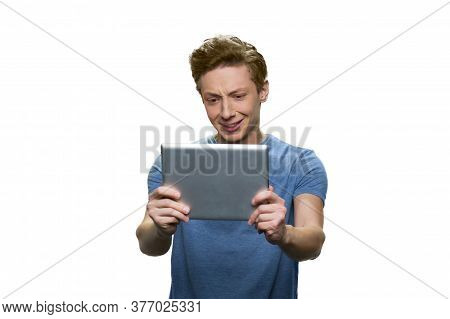 Teen Skinny Guy Is Holding Tablet Pc. Facial Expression Of Discontent. Isolated On White Background.