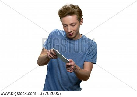 Enthusiastic Teenage Boy Is Playing Video Game On His Phone. Portrait Of Young Gamer Playing On His