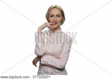 Alluring Woman In White Blouse Holding Her Finger Near Lips And Standing Against White Background. C