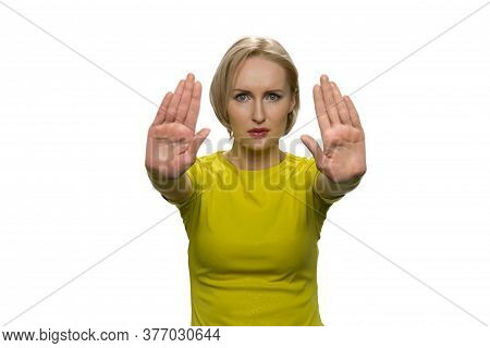 Young Woman In Yellow Turtleneck Making Stop Gesture With Both Hands On White Background. No Gesture