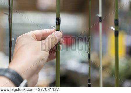 Hand Takes Fishing Rod Or Spinning In The Store. Man Selecting Fishing Rod In The Sports Shop Indoor