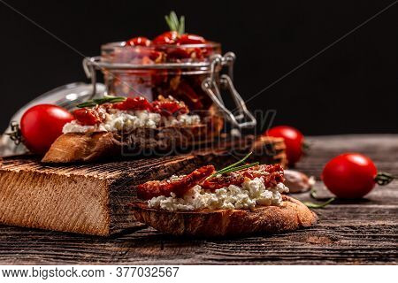 Bruschettas With Sun Dried Tomatoes And Ricotta Diet Cheese On A Wooden Background.
