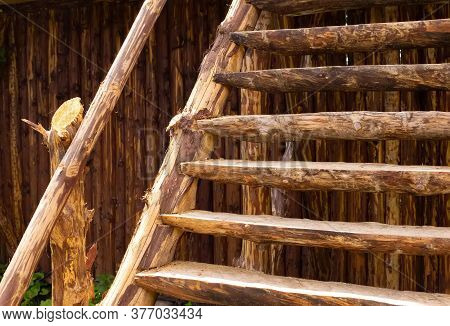 Old Brown Orange Rustic Construction. Plank Log Stairs Stairway Ladder In Front Of Natural Wooden Fe