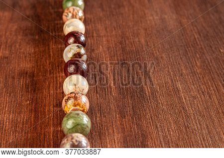 Beads Made Of Ural Jasper On Wooden Background With Empty Space For Text