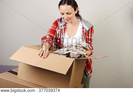 Unpacking The Parcel. The Woman Opens The Box And Happily Takes Out The Purchases From The Online St
