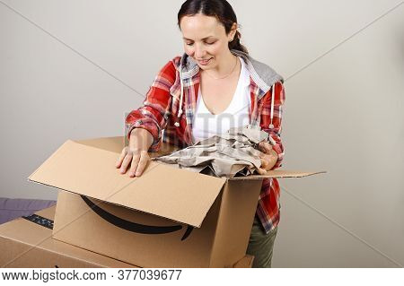 July 12, 2020, Bologna Italy. Unpacking The Amazon Parcel. The Woman Opens The Box And Happily Takes