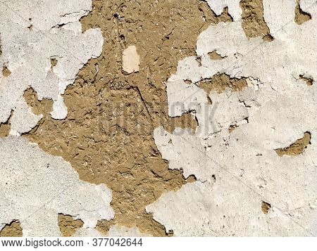 Close-up Background Of The Wall Of An Old House Made Of Clay Mixed With Straw. Old Type Of Construct
