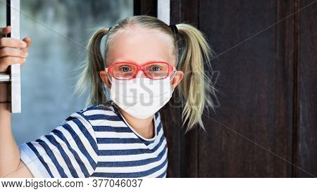 Little Child Looking Out Opened Door After Staying At Home Due Banned Street Activity. Kid Wearing M