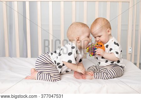 Two Twin Babies 8 Months Old Play In The Crib, Early Development Of Children Up To A Year, The Conce