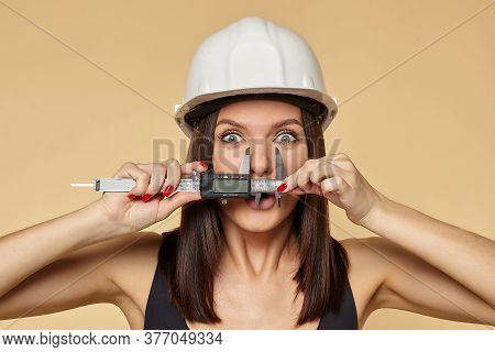 Woman In A White Protective Construction Helmet Holds A Caliper. Performs The Measurement Of The Nos