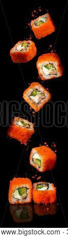 California rolls sushi with salmon, cucumber, avocado, cream cheese, red masago caviar in levitation over black background. Sushi menu, Japanese food.