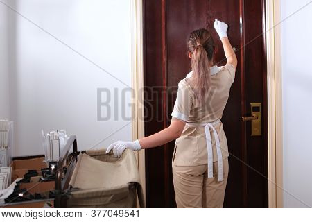 Room Service. A Uniformed Maid Enters The Room. Trolley For The Maid With Bathroom. Copy Of The Spac