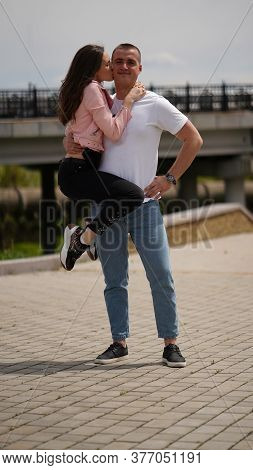 Kissing Couple In Park, Strong Man Holding Girl On One Arm, Woman Kissing Him . Kiss, Love And Relat
