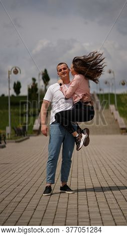 Kissing Couple In Park, Strong Man Holding Girl On One Arm, Woman Want To Kiss Him . Kiss, Love And