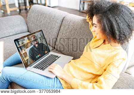 Cheerful African-american Girl Lays On The Comfortable Sofa In Stylish Living Room And Using Trendy