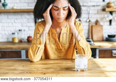 Close-up Shot Of A Tired Girl With Strong Headache. She Has Her Eyes Closed And A Glass Of Water In