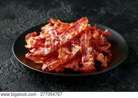 Fried Crunchy Streaky Bacon Pieces In A Black Plate