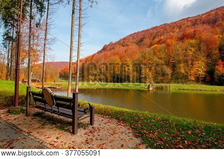 Small Lake In Autumn Park. Forest On The Hills In Fall Colors. Green Grass On The Shore. Beautiful N