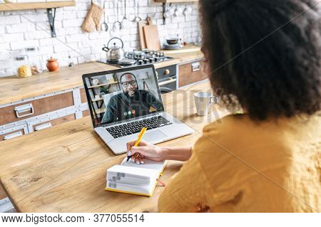 A Female Student Studies Online. An African Woman Is Watching Online Classes And Writing A Syllabus