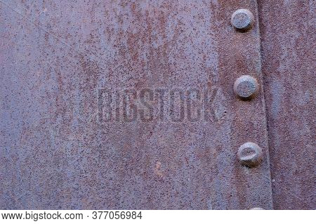 Fragment Rusty Riveted Hull Of An Old Ship. Large Metal Rivets Metal With Corrosion. Outdated Shipbu