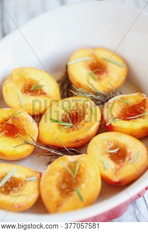 Fresh Homemade Roasted Peaches Baked In Brown Sugar And Fresh Rosemary Sprigs. Selective Focus With