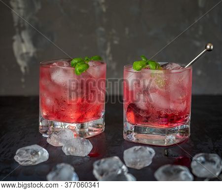 Refreshing Cherry Drink On Mineral Water In Two Glass Glasses With Mint Sprigs On A Dark Background