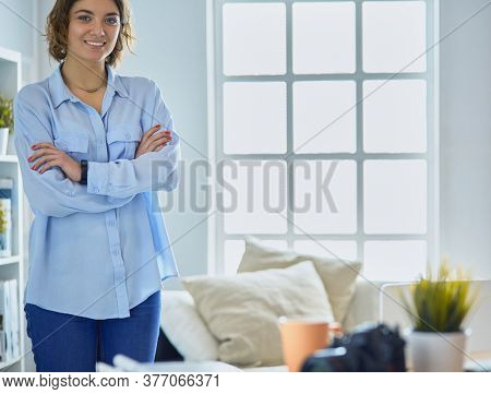Portrait of smiling young woman with dslr photo camera standing in loft apartment