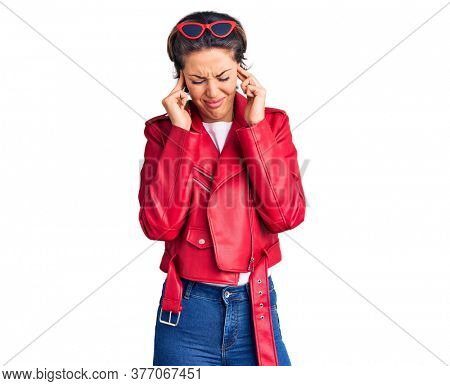 Young beautiful woman wearing red leather jacket covering ears with fingers with annoyed expression for the noise of loud music. deaf concept.