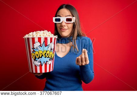 Young blonde woman wearing 3d glasses and eating pack of popcorn watching a movie on cinema doing money gesture with hands, asking for salary payment, millionaire business