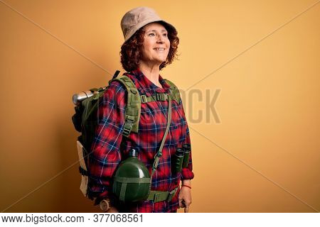 Middle age curly hair hiker woman hiking wearing backpack and water canteen using binoculars looking away to side with smile on face, natural expression. Laughing confident.
