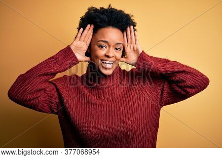 Young beautiful African American afro woman with curly hair wearing casual turtleneck sweater Smiling cheerful playing peek a boo with hands showing face. Surprised and exited