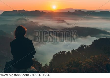 Woman Tourist Is Sitting On A Rocky Mountain, Looking At The Beautiful Of The Sunrise And The Fog Co
