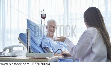 Happy Woman Doctor Checking Blood Pressure Test Of Sick Old Female Senior Elderly Patient Lying In B