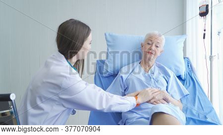 Happy Woman Doctor Talking Encourage To Sick Old Female Senior Elderly Patient Lying In Bed In Hospi