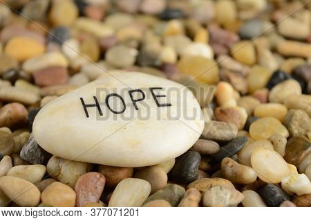 An Engraved River Stone With The Word Hope Giving Spiritual Ambience To The Scene.