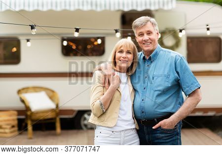 Portrait Of Mature Couple Embracing Near Their Motorhome At Campground, Copy Space. Panorama