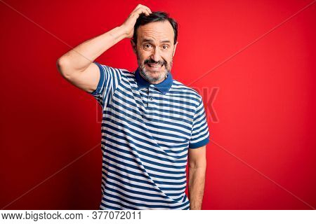 Middle age hoary man wearing casual striped polo standing over isolated red background confuse and wonder about question. Uncertain with doubt, thinking with hand on head. Pensive concept.