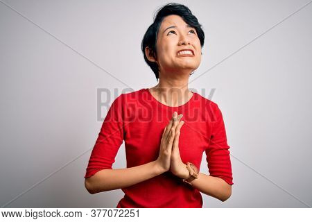 Young beautiful asian women wearing casual red t-shirt standing over isolated white background begging and praying with hands together with hope expression on face very emotional and worried. Begging.