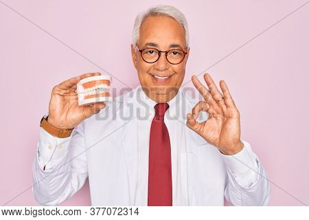 Middle age senior grey-haired dentist man holding prosthesis denture over pink background doing ok sign with fingers, excellent symbol