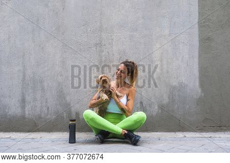 Spanish Woman Holding Dog After Exercising Outdoors. Sport Concept.