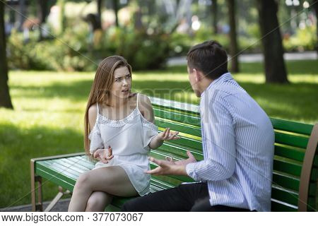 Relationship Problems Concept. Millennial Couple Having Argument On Bench At Summer Park