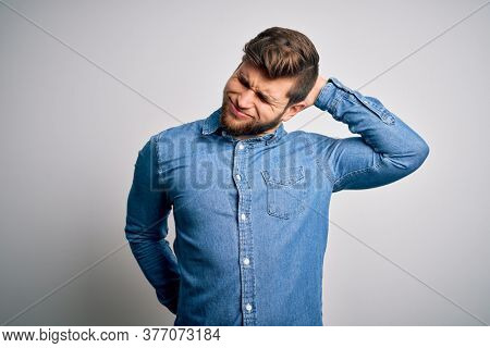 Young handsome blond man with beard and blue eyes wearing casual denim shirt Suffering of neck ache injury, touching neck with hand, muscular pain
