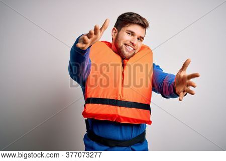 Young blond tourist man with beard and blue eyes wearing lifejacket over white background looking at the camera smiling with open arms for hug. Cheerful expression embracing happiness.