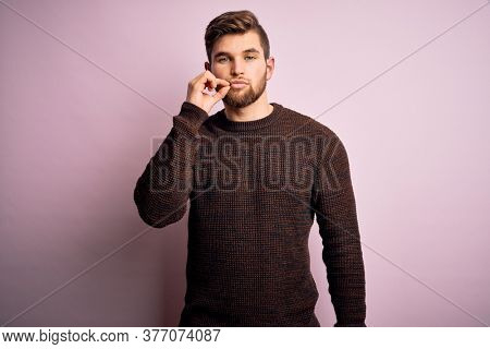 Young blond man with beard and blue eyes wearing casual sweater over pink background mouth and lips shut as zip with fingers. Secret and silent, taboo talking