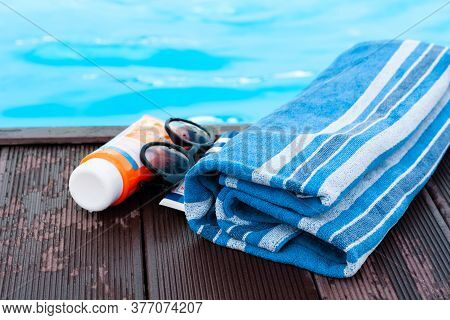 Sun Glasses, Tube Of Sunscreen Cream, Blue Towel Near Swimming Pool, Tropical Background